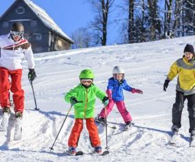 Familie übt auf der Skipiste das Skifahren